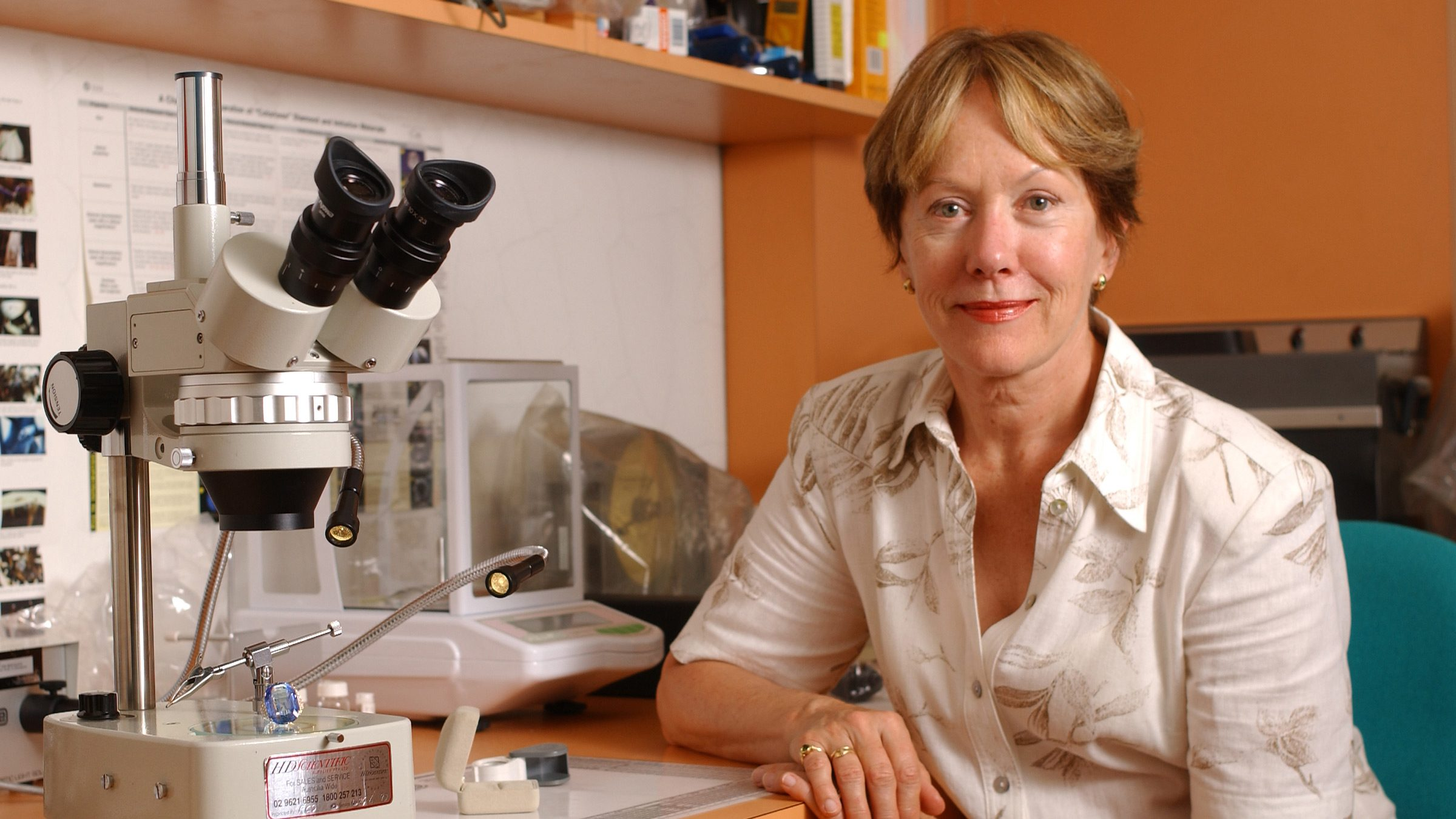 Photo of Gayle Sutherland in front a of desk containing a microscope